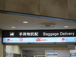 空港宅配サービスのQLライナーにてスーツケースの受け取り